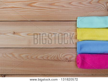 Multicoloured rags for cleaning on wooden table