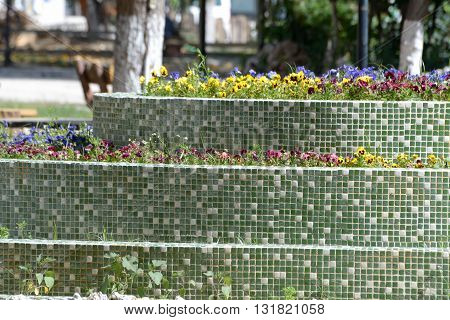 Green white mosaic flowerbed with spring flowers in it