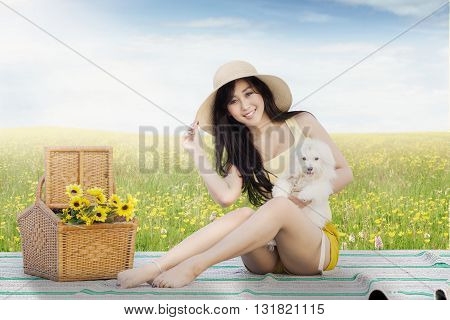 Picture of a pretty young model sitting on the meadow while holding a maltese dog and smiling at the camera
