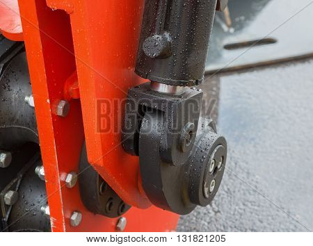 Detail of hydraulic bulldozer piston excavator arm with raindrops