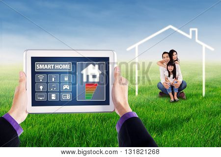 Applications of smart house technology on the digital tablet screen with happy family sitting under a house symbol