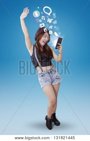 Full length of beautiful teenage girl using smartphone to enjoy entertainment while standing with blue background