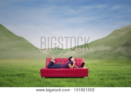 Thoughtful woman lying on couch with laptop - shot outdoor with mountain view