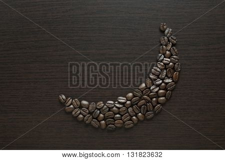 Roasted black coffee beans arranged in a moon shape on dark background. Coffee beans in moon shape - Ramadan food concept.