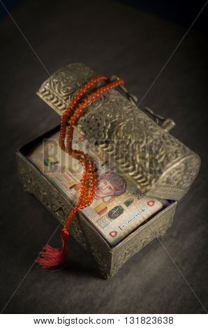Omani Riyals in an ornamental, vintage treasure box. 'Islamic Finance' - creative concept.