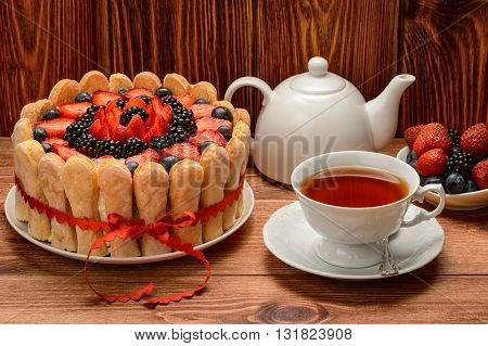 Biscuit cake with strawberries, blueberries and blackberries and cup ot tea on brown wooden background.