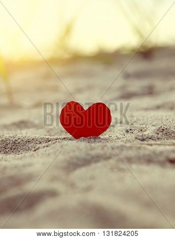 Toned Photo of the Red Heart in the Sand at the Evening Beach