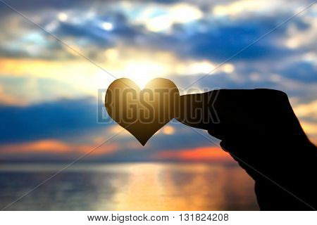 Toned Photo of Heart Shape in the Hand on the Sky Background