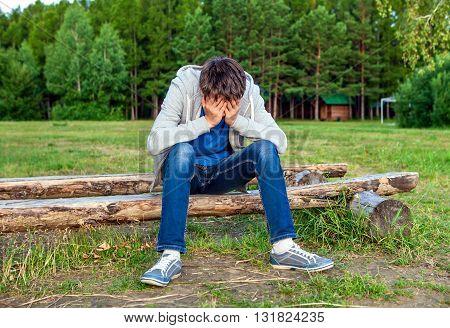 Sad Young Man sit on the Log outdoor