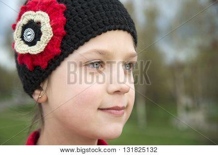 close up portrait of girl in black knitwear cap outdoor
