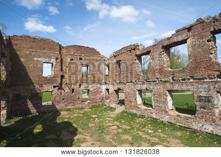 ancient ruined red brick walls under bright blue sky