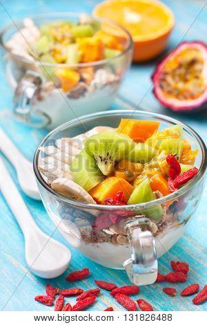 Dietary breakfast. Muesli yoghurt goji berries tropical fruits: mango kiwi pineapple passion fruit in cup on a blue background