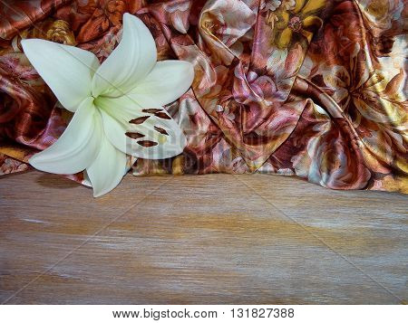 on a wooden Board is silk with abstract figures in brown tones, ying next to a Lily flower