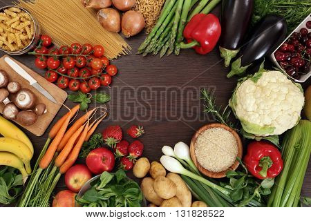 Photo of a table top full of fresh vegetables fruit and other healthy foods with a space in the middle for text.