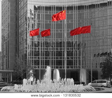 Glass fronted building with fountain and chinese flags in Beijing China