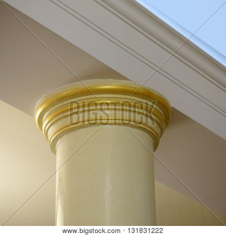 Architectural detail of classic column pillar on white ceiling background