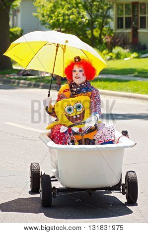 WEST ST. PAUL, MINNESOTA - MAY 21, 2016: Colorful clown holding umbrella sitting in bathtub entertains crowd at annual West St. Paul Days Grande Parade in West St. Paul on May 21, 2016.