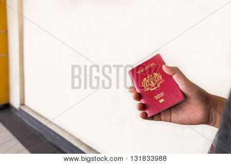 Hand Holding Malaysia International Passport Against Wall Background