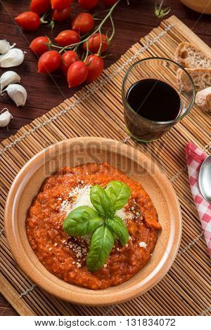 Tomato soup served in a crock pot with a basil leaf as decoration