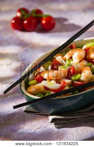 Salad of shrimps and chopsticks inside an oval bowl