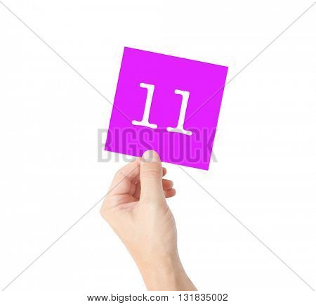 11 written on a card held by a hand