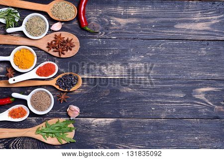 Powder spices & herbs on spoons in black wooden table background