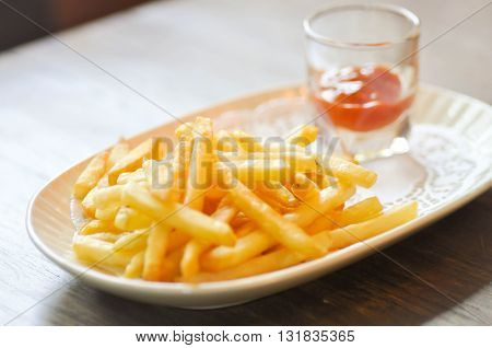 French fries dish and ketchup dip in soft focus