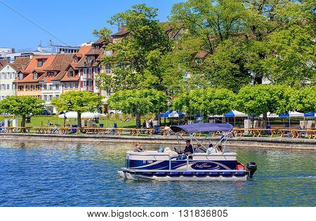 Zug, Switzerland - 6 May, 2016: people in a boat on Lake Zug with the city of Zug in the background. Lake Zug (German: Zugersee) is a lake in central Switzerland, situated between Lake Lucerne and Lake Zurich.