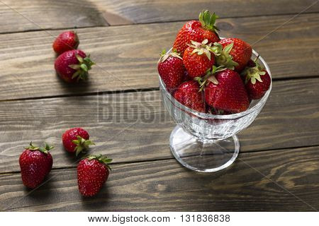 ripe strawberries in a cup of ice cream and berries on a wooden table