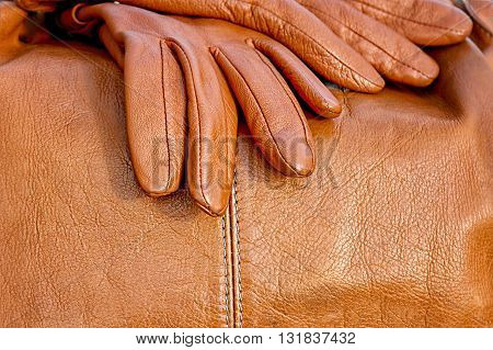 orange leather gloves lie on the bag