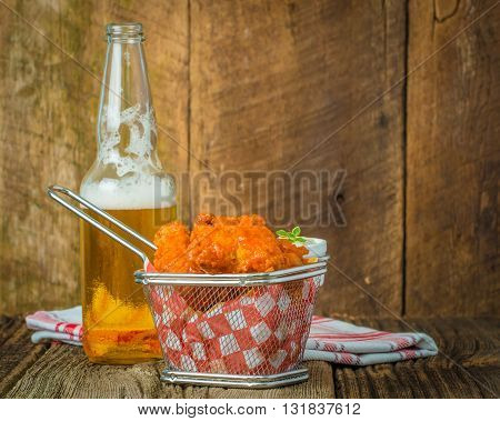 Spicy buffalo style wings in a basket served with cold beer.