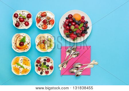 6 bowls of differently dressed yogurts displayed vertically in 2 rows of 3 pc. near plate of berries 6 spoons napkins on light blue background right empty space. Six yogurts ready to eat. Top view.