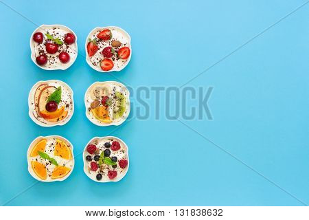 Left 6 different yogurts displayed vertically in 2 rows of 3 pieces right empty space on light blue background. Six yogurts and empty space. Horizontal. Top view.