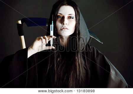 Woman death reaper with syringe over black background.