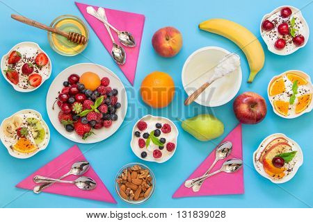 6 bowls of yogurt dressed with different ingredients fruit berries nuts honey and 6 spoons napkins on light blue background. Six differently dressed yogurts and ingredients. Horizontal. Top view.