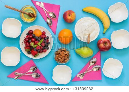 Greek yogurt around a variety of fruits and berries nuts honey and 6 empty bowls 6 spoons and napkins on a light blue background. Yogurt and a variety of ingredients for it. Horizontal. Top view.