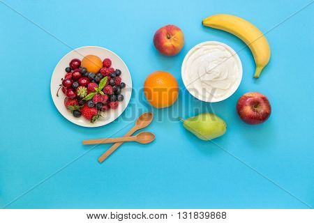 Greek yogurt around orange banana pear peach apple plate with strawberries raspberries blueberries and two wooden spoons on light blue background. Horizontal. Top view.