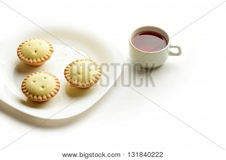 Shortcrust tartlets on a plate with a cup of black tea isolated on white background