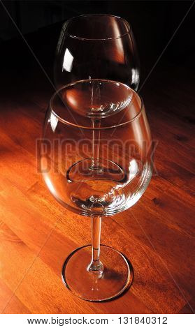 two wine glasses on a wooden table, black background