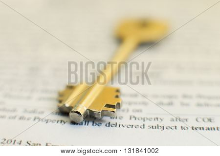 house key lying on a contract of house sale lease insurance or mortgage in a real estate concept viewed low angle with focus to the tip.