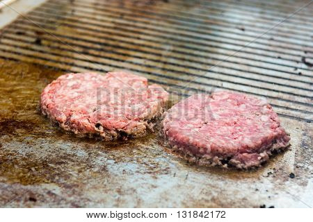 Chef preparing tasty burgers at outdoor stand. Minced meat on bbq.