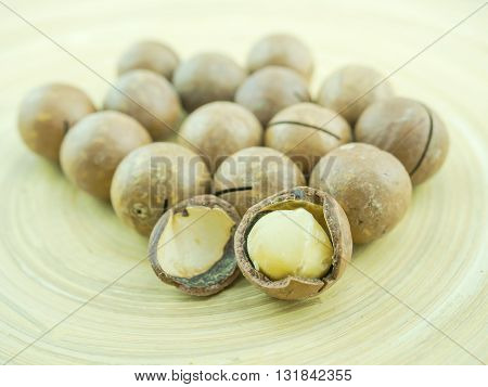 Group of organic macadamia nuts on wooden plate