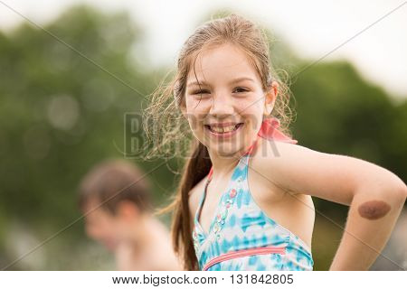 Caucasian girl wearing swimsuit smiles at camera during outside play