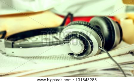 Big black silver headphones on newspapers for happy