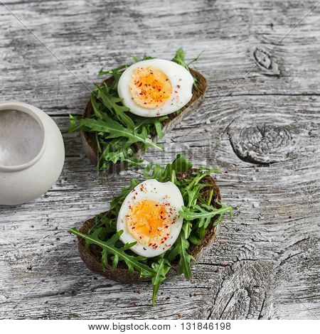 Sandwich with arugula and boiled egg on a wooden board. Healthy breakfast or snack