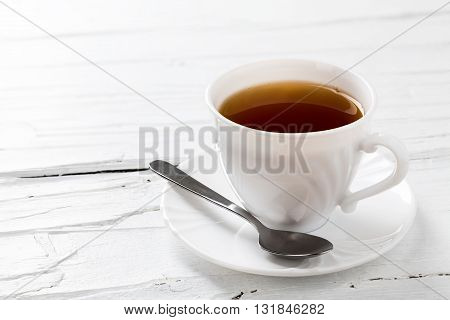 Cup of tea on white wooden background closeup.