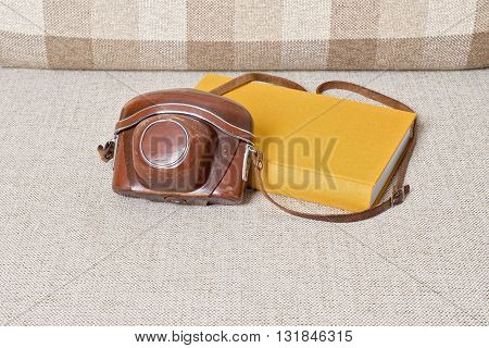 old vintage camera in brown case and yellow book on the sofa
