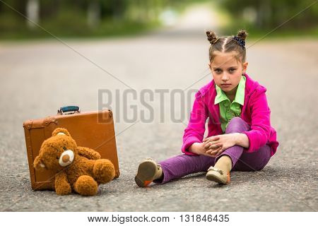 Little girl sitting on the road with a suitcase and a Teddy bear.