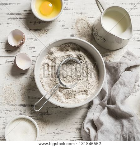 Whole-wheat flour in white bowl milk eggs on a light wooden background. Baking rustic background