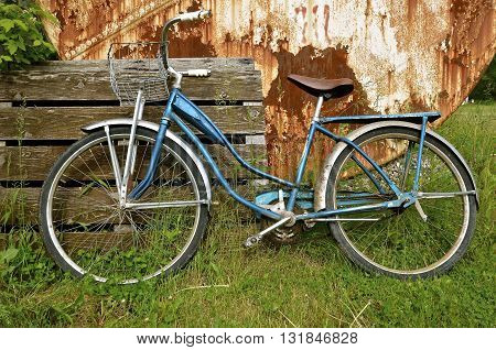 An old classic girl's bicycle lays against a wood pallet and rusty oil tank